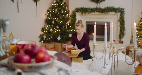 Young-Woman-Positioning-Christmas-Presents-Under-Tree