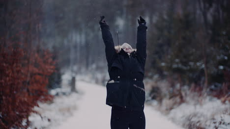 Positive-Woman-Jumping-On-Snow-And-Playing-With-Scarf-In-Winter-3