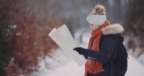 Female-Tourist-Reading-Map-In-Woods-In-Winter