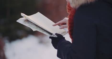 Female-Tourist-Reading-Map-In-Woods-In-Winter-4