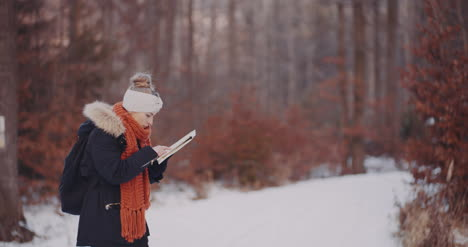 Female-Tourist-Reading-Map-In-Woods-In-Winter-5