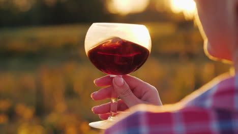 Woman-Holds-Red-Wine-by-Setting-Sun