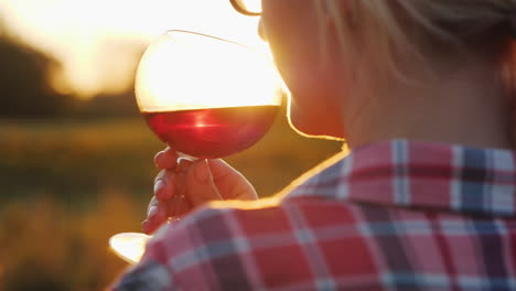 Woman-Smelling-Red-Wine-at-Sunset