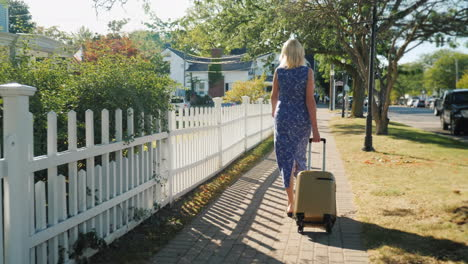 Woman-With-Suitcase-Walking-Down-Street