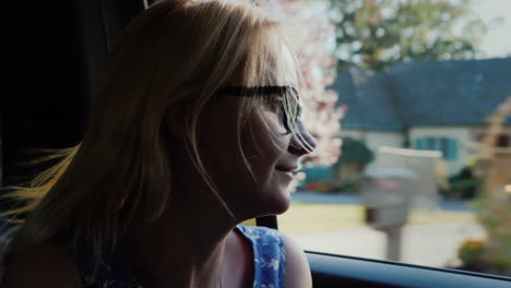Woman-Looks-Out-Car-Window-on-Sunny-Day