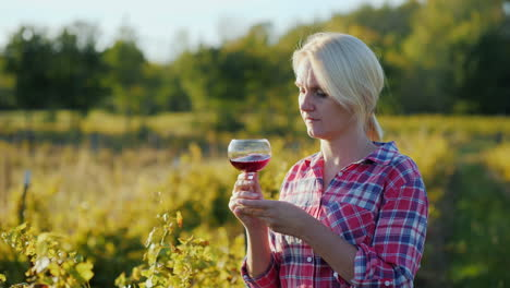 Woman-Smelling-Red-Wine-in-Vineyard