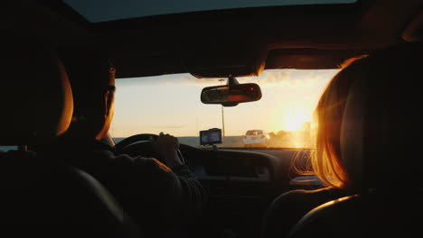 Couple-Drive-on-Highway-at-Sunset