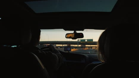 Couple-Driving-Car-at-Sunset