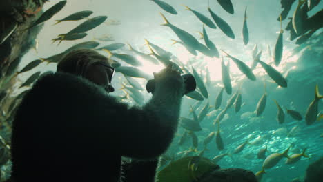 Woman-Takes-Pictures-in-Aquarium-Tunnel