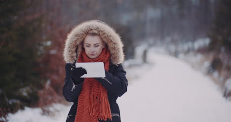 Positive-Woman-Using-Digital-Tablet-In-Winter-Outdoors-1