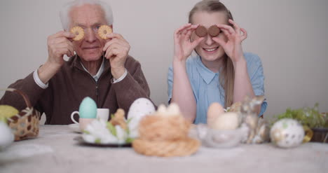 Senior-Man-Smiling-Chererful-Grandfather-And-Granddaughter-Playing-With-Cakes-And-Smile-
