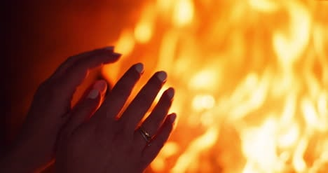 Woman-Warms-Hands-By-The-Fireplace-At-Home