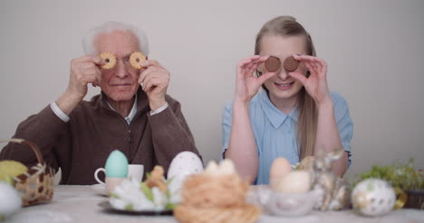 Senior-Man-Smiling-Chererful-Grandfather-And-Granddaughter-Playing-With-Cakes-And-Smile-1