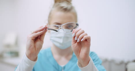 Female-Doctor-Wearing-Protective-Mask-On-Face-And-Cleaning-Glasses-Doctor-At-Healtcare-Clinic