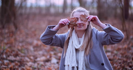 Smiling-Woman-Hiding-Eyes-With-Leaves-In-Autumn