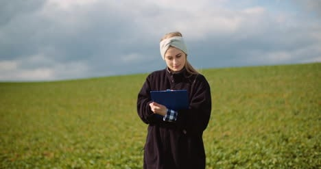 Female-Farmer-Examining-Oilseed-Rape-Field-21