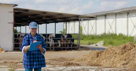 Farmer-Gesturing-While-Writing-On-Clipboard-Against-Barn