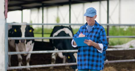 Farmer-Gesturing-While-Writing-On-Clipboard-Against-Barn-1