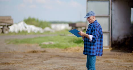 Farmer-Gesturing-While-Writing-On-Clipboard-Against-Barn-12