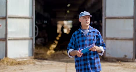 Farmer-Gesturing-While-Writing-On-Clipboard-Against-Barn-24