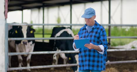 Farmer-Gesturing-While-Writing-On-Clipboard-Against-Barn-26