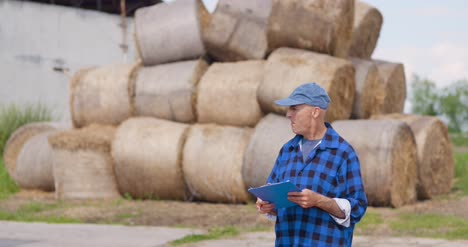 Farmer-Gesturing-While-Writing-On-Clipboard-Against-Barn-27