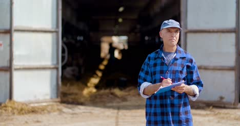 Farmer-Gesturing-While-Writing-On-Clipboard-Against-Barn-28
