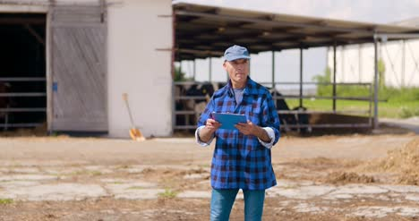 Farmer-Gesturing-While-Writing-On-Clipboard-Against-Barn-4