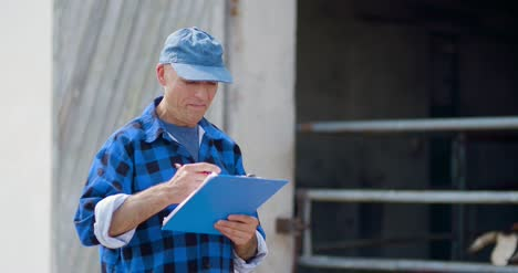 Farmer-Gesturing-While-Writing-On-Clipboard-Against-Barn-5