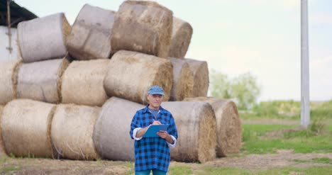 Farmer-Gesturing-While-Writing-On-Clipboard-Against-Barn-6