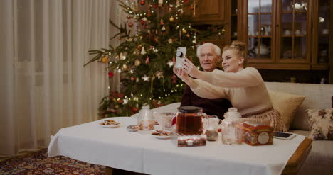 Cheerful-Woman-Taking-Selfie-With-Grandfather-During-Christmas