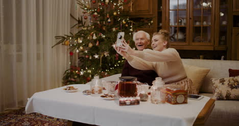 Cheerful-Woman-Taking-Selfie-With-Grandfather-During-Christmas-1