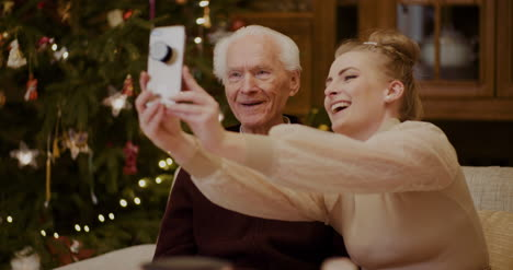 Cheerful-Woman-Taking-Selfie-With-Grandfather-During-Christmas-3