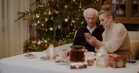 Woman-Teaching-Grandfather-To-Use-Cellphone-In-Christmas