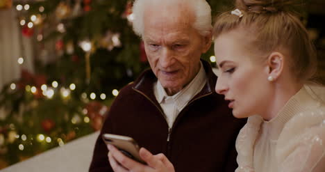 Female-Teaching-Grandfather-To-Use-Cellphone-In-Christmas