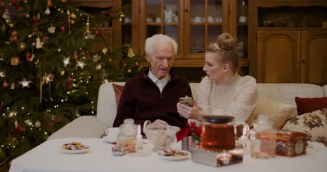 Woman-Teaching-Grandfather-To-Use-Smartphone-In-Christmas