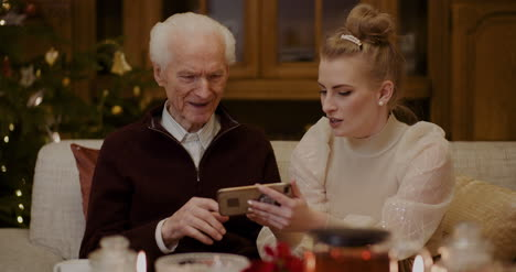 Woman-Teaching-Grandfather-To-Use-Smartphone-In-Christmas-1