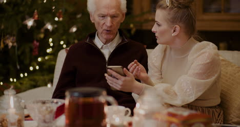 Woman-Teaching-Grandfather-To-Use-Smartphone-In-Christmas-2