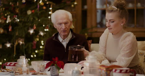 Woman-Pouring-Black-Coffee-In-Cup-For-Grandfather-During-Christmas