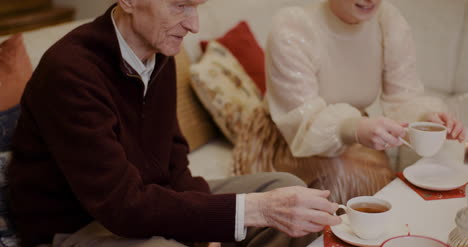 Woman-Pouring-Black-Coffee-In-Cup-For-Grandfather-During-Christmas-1