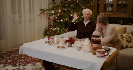 Woman-Listening-To-Grandfather-At-Home-During-Christmas-1