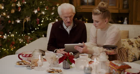 Grandfather-Talking-While-Granddaughter-Holding-Digital-Tablet-1