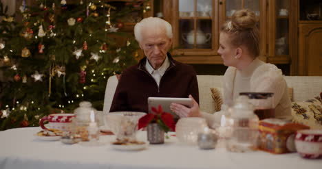 Grandfather-Talking-While-Granddaughter-Holding-Digital-Tablet-3