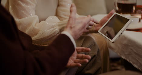 Granddaughter-And-Grandfather-Discussing-Over-Digital-Tablet-At-Home