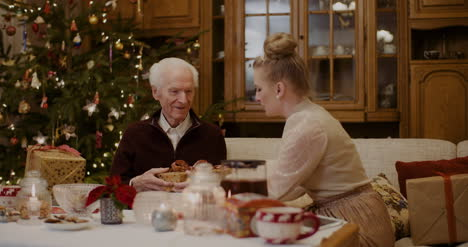 Young-Woman-Giving-Christmas-Present-To-Grandfather-At-Home