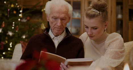 Granddaughter-And-Grandfather-Looking-At-Photo-Album-In-House