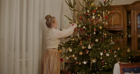 Woman-Decorating-Christmas-Tree-At-Home-1