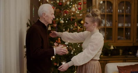 Woman-Giving-Christmas-Present-To-Grandfather-At-Home-5