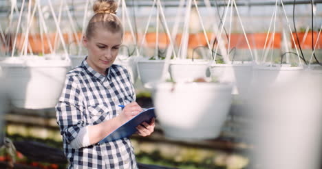 Agriculture-Business-Smiling-Gardener-Working-With-Flowers-In-Greenhouse-3