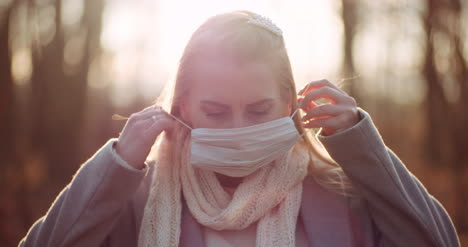 Woman-Putting-On-Protective-Mask-Against-Coronavirus